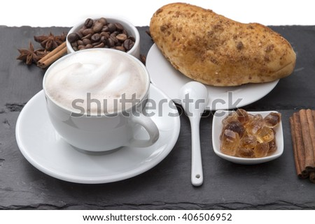 Cup of coffee cappuccino with milk foam on a saucer, fresh baked bun, caramelized sugar, coffee beans, cinnamon. Popular morning Breakfast. on a black background plates of slate. - stock photo