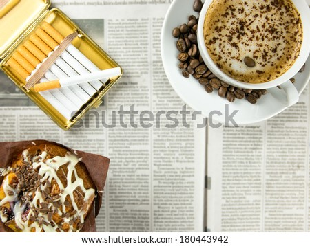 Cup of coffee, chocolate muffin and cigarettes arranged on a newspaper - stock photo
