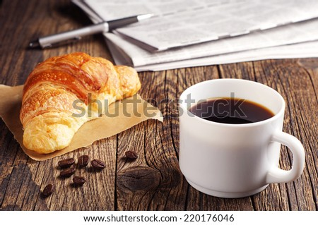 Cup of coffee, croissant and newspaper on wooden table - stock photo