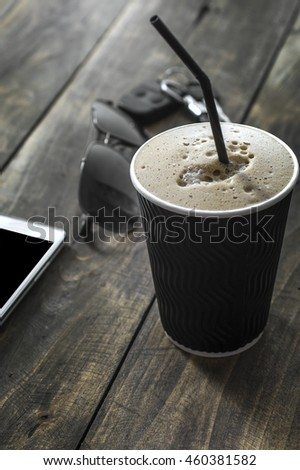 Cup of  coffee drink with sunglasses and mobile phone on wooden  table