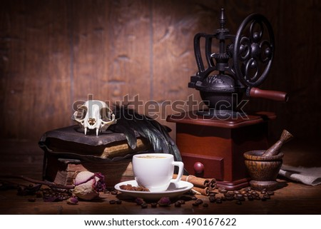 Cup of coffee, dry rose, old books, crow quills and coffee grinder on wooden table. Vintage still life.