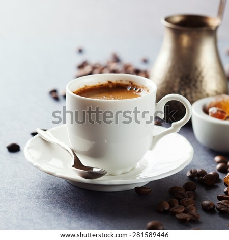 Cup of coffee espresso, brown sugar and roasted beans on dark background, selective focus