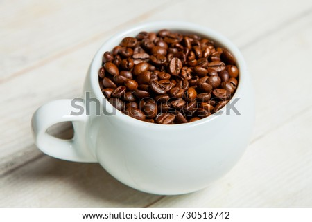 Cup of coffee full of coffee beans. Close-up