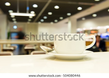 Cup of coffee in caf�© interior with blur background