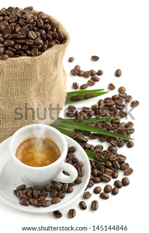 cup of coffee, jute bag and coffee beans on a green leaf - stock photo