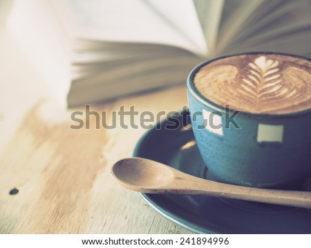 cup of coffee latte art  with book in coffee shop vintage color - stock photo