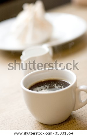cup of coffee, milk and meringue on wooden table - stock photo