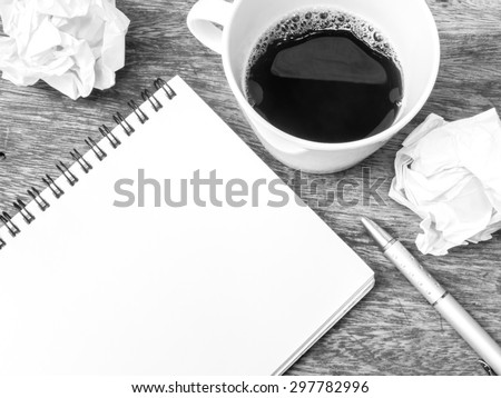 Cup of coffee , notepad and crumpled paper on wooden table, black and white color - stock photo