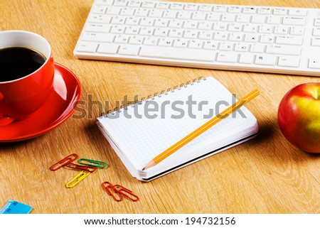 Cup of coffee notepad and keyboard on wooden table - stock photo