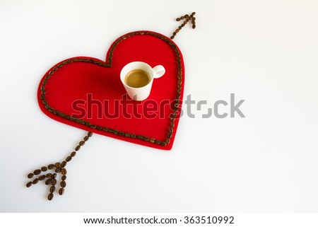Cup of coffee on a red felt heart with coffee beans around and arrow - stock photo