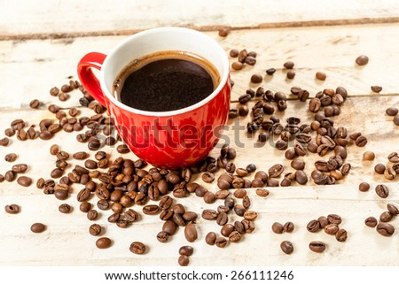 Cup of coffee on a wooden background with coffee beans. - stock photo