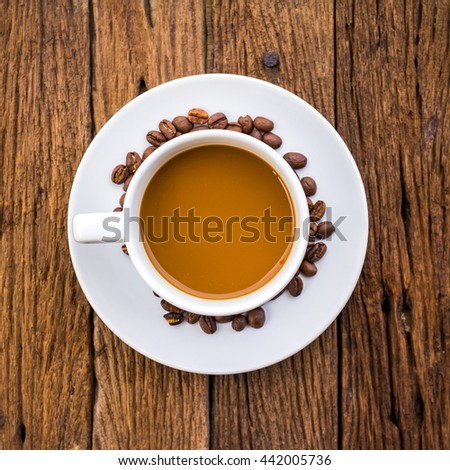 Cup of coffee on a wooden desk with coffee beans, top view - stock photo