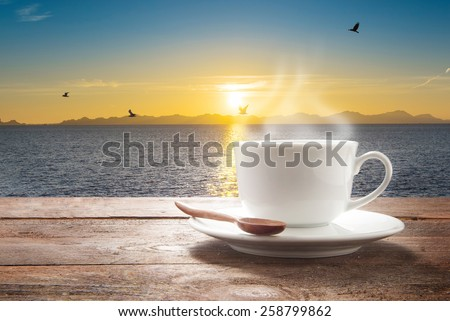 Cup of coffee on a wooden table at sea view. - stock photo