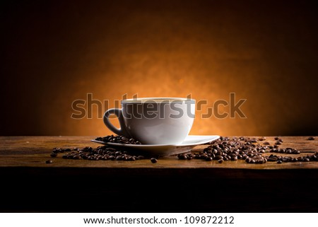 cup of coffee on a wooden table on dark background - stock photo