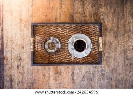 Cup of coffee on a wooden table with glass of water in the wooden tray. The view from the top - stock photo