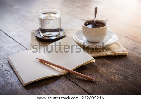 Cup of coffee on a wooden table with glass of water on the Sackcloth bags and notebook and pencil - stock photo