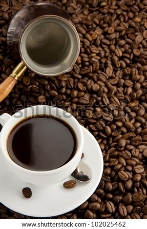cup of coffee on beans as background - stock photo