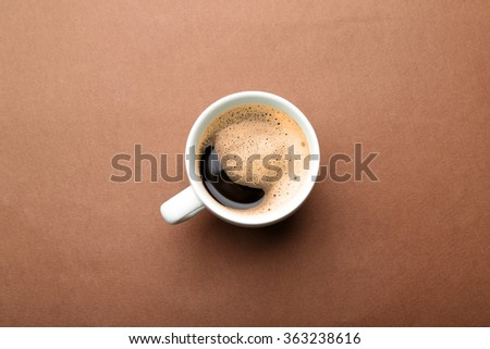 Cup of coffee on brown background, top view - stock photo