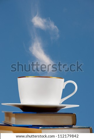 Cup of coffee on pile of books with blue background. Background is actually sky with fluffy white cloud - stock photo