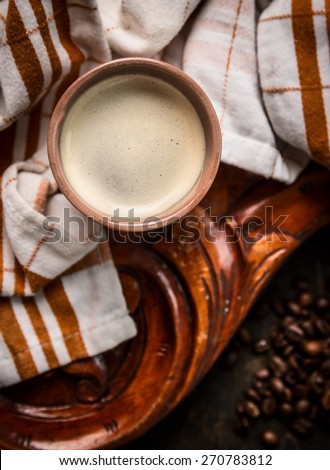 cup of coffee on rustic wooden background with towel, top view