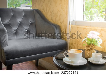 cup of coffee on table and old chair in cafe at morning