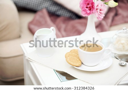 Cup of coffee on table in living room