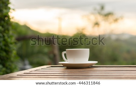 Cup of coffee on table outdoor relaxing on morning light.