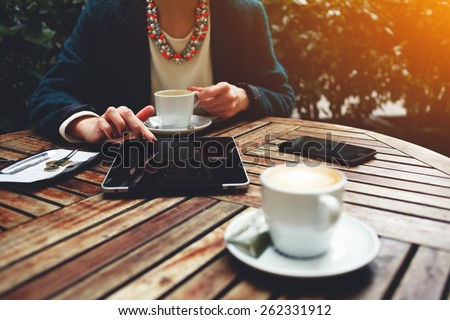 Cup of coffee on the foreground with elegant woman using busy touch screen tablet and drinking cappuccino at the coffee shop, bill check and mobile phone near, flare sun light - stock photo