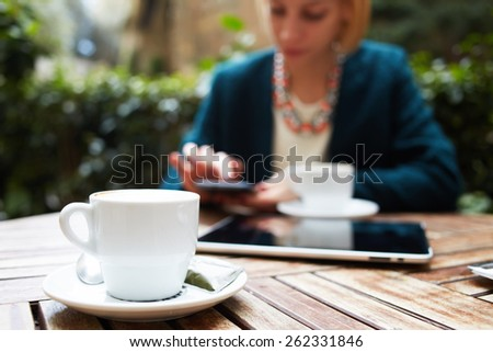Cup of coffee on the foreground with elegant young woman using busy touch screen tablet at the coffee shop wooden table, work break of business people - stock photo