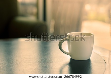 cup of coffee on the table in coffee shop vintage style - stock photo