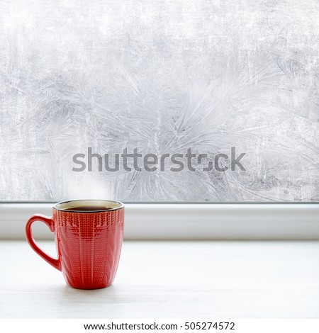 Cup of coffee on the window sill. In the background frosty pattern on window as a Christmas background
