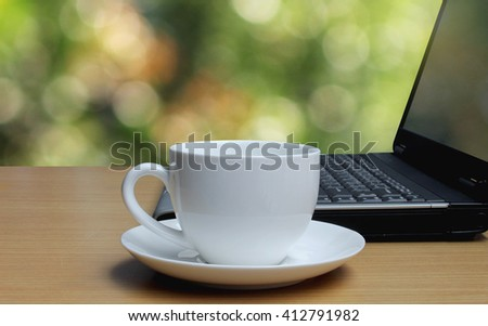 Cup of coffee on the wooden floor and bokeh background.