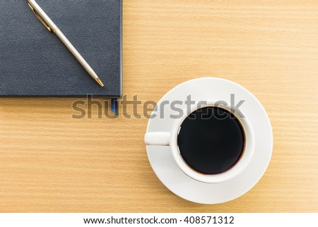 Cup of coffee on wood deck and notebook - stock photo