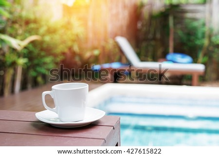 cup of coffee on wood with blurred pool background - stock photo