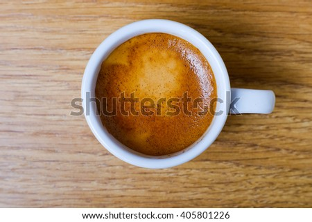 Cup of coffee on wooden background table, top view. Close-up top view of a white cup of black coffee, espresso on wooden table.  - stock photo