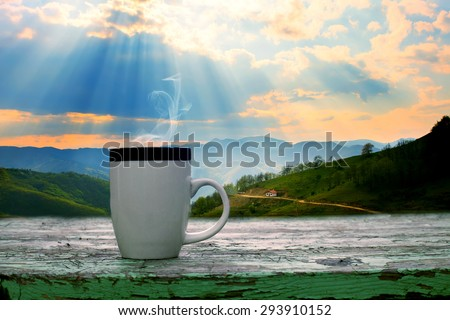 cup of coffee on wooden table dramatic sky over the mountains in background  - stock photo