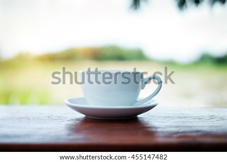 Cup of Coffee on wooden table in the garden in morning light