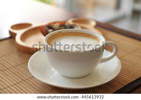 Cup of coffee on wooden table with confectioners atmosphere.