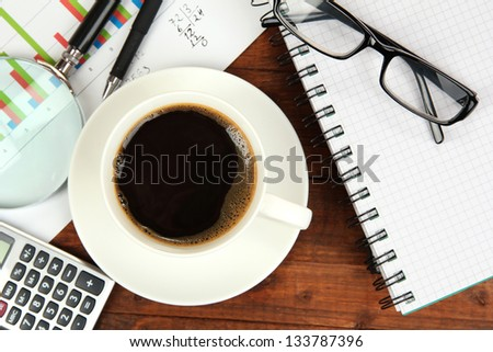 Cup of coffee on worktable covered with documents close up - stock photo