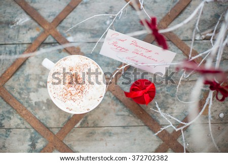 Cup of coffee or hot chocolate with whipped cream for Valentine breakfast with greeting card and round red jewelry box with ribbon and against the vintage background