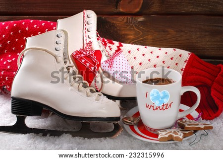cup of coffee,pair of white ice skates and wool sweater on snow - stock photo
