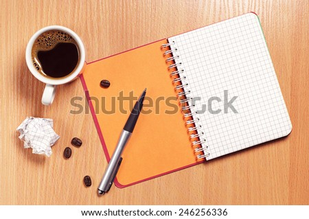 Cup of coffee, pen, notepad and crumpled paper on desk, top view - stock photo