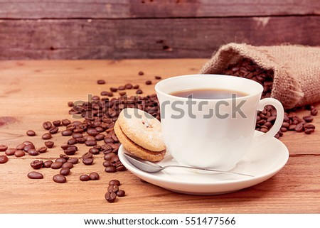 Cup of coffee, saucer with cookies, roasted coffee beans in sack over on old wooden table. Tinted toned image