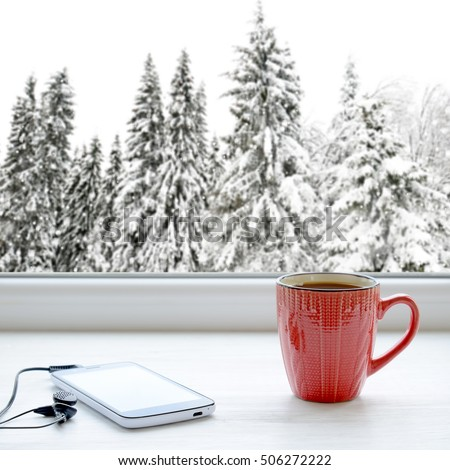 Cup of coffee, smartphone and headphones on a windowsill. In the background, a beautiful winter forest in snow
