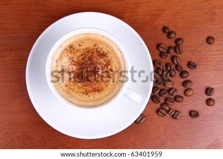 Cup of coffee sprinkled with cinnamon and some coffee beans on a wooden background - stock photo