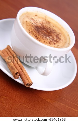 Cup of coffee sprinkled with cinnamon and with cinnamon sticks on wooden background - stock photo