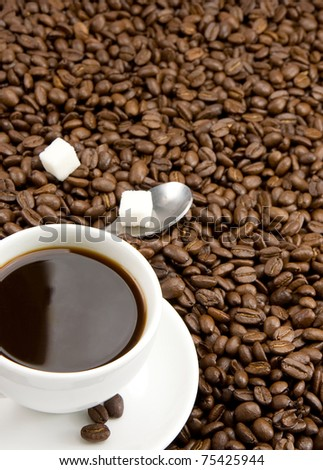 cup of coffee, sugar and spoon on roasted beans - stock photo