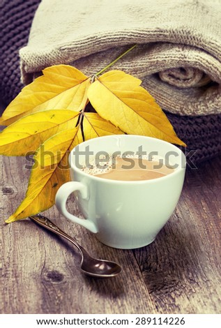 cup of coffee, warm woolen things autumn leaves on a wooden background (vintage style, toning) - stock photo