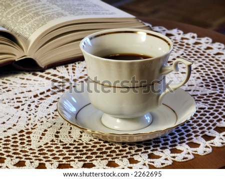 Cup of coffee, white tablecloth and a book.