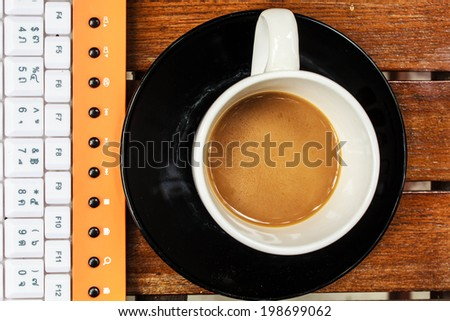 Cup of coffee with a working computer. - stock photo